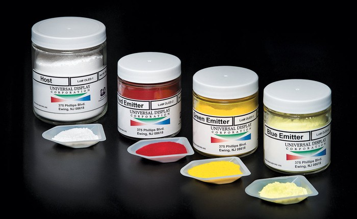 Four jars containing Universal Display's OLED host material, and red, green, and blue emitters.