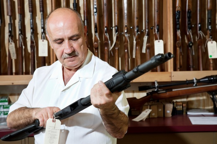 Man looking at shotgun in gun store.