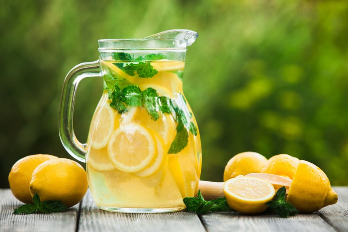 A pitcher of lemonade surrounded by fresh lemons on a wood table outdoors.