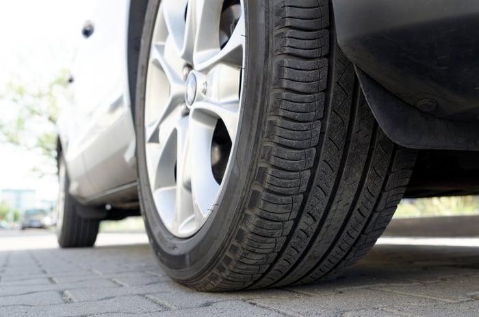 Close up of a car tire in a driveway.