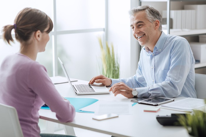 Woman sitting across a deskfrom smiling man at laptop