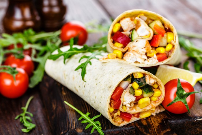 Two burritos garnished with tomatoes