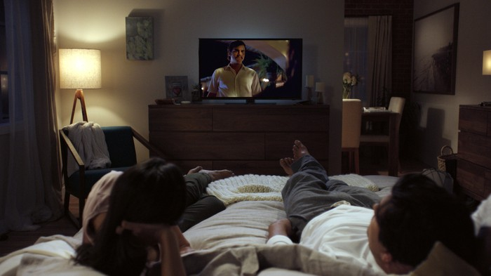 A couple watching TV in bed.