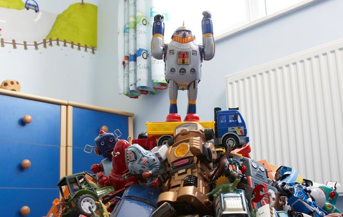 A toy robot stands with its arms raised atop a pile of toys