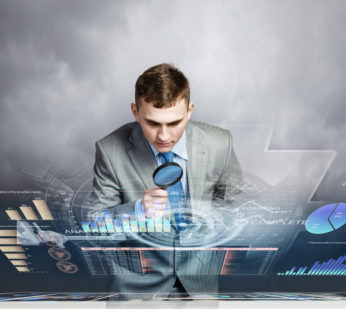 Businessman looking at data using a magnifying glass.