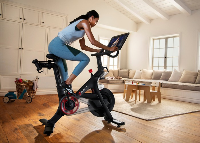 Woman riding a Peloton stationary bike in a living room.