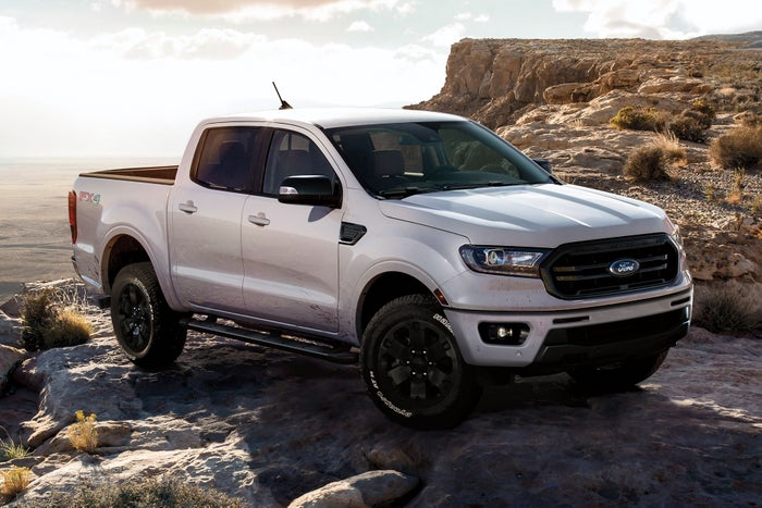 A white Ford Ranger parked near a cliff