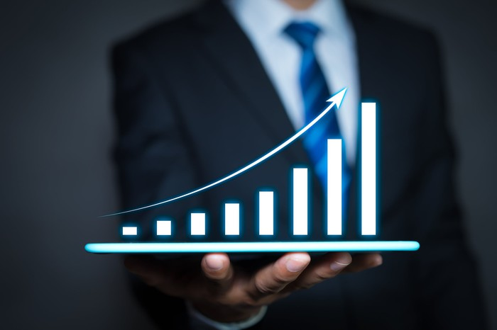 A person in a suit holding an upwardly sloping digital bar chart.