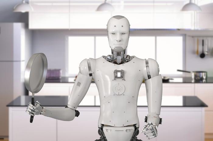 Robot holding frying pan in kitchen