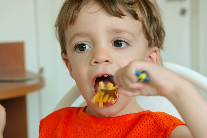 A little boy eating mac and cheese.
