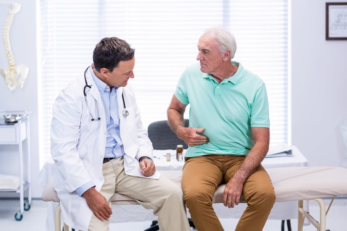Older man sitting next to a doctor, clutching his stomach.