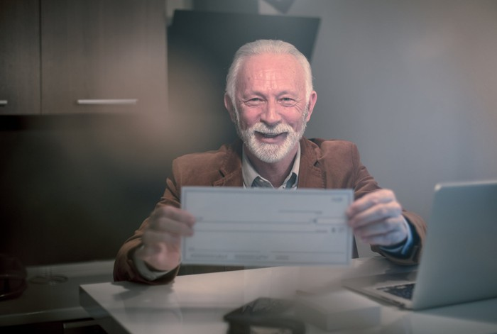 Smiling older man holding up a blank check
