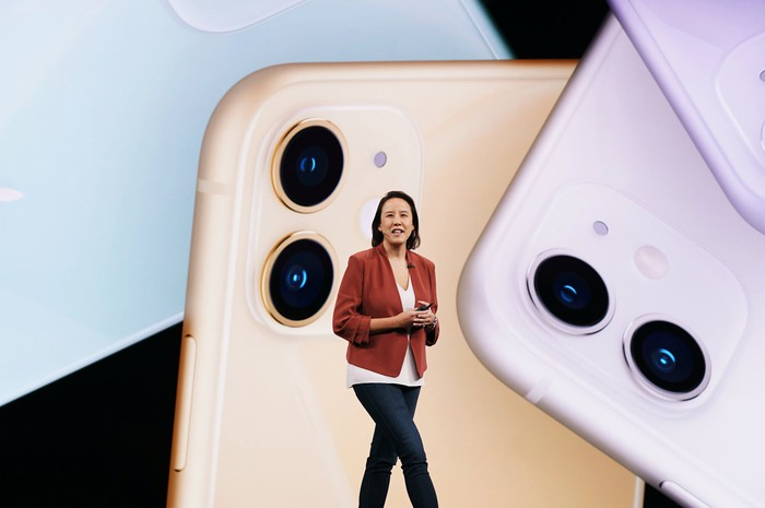A woman standing in front of a promotional image of the iPhone 11.