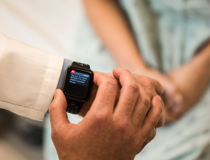 A physician reviewing an Apple Watch notification as a patient sits on a bed nearby.