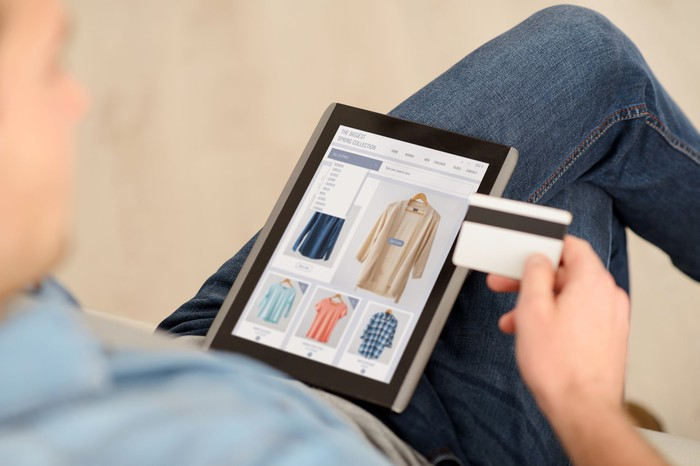 A man holds a credit card while looking at clothes on a tablet.