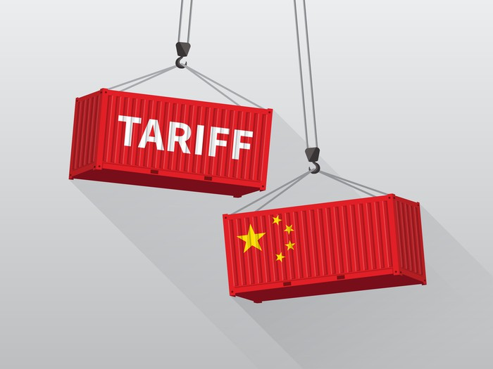 Two red shipping containers, hoisted by cranes, about to collide. One is painted with symbols of the Chinese flag, while the other bears the word tariff.