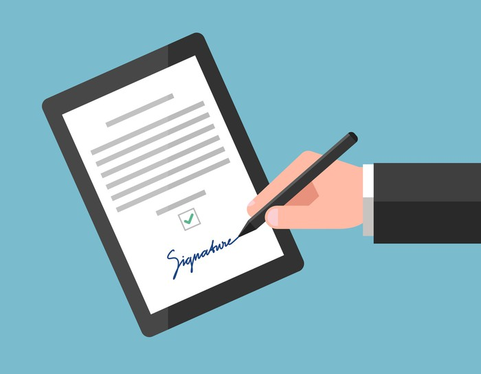 Illustration: Close-up of a man using a stylus to sign an agreement on a tablet computer.