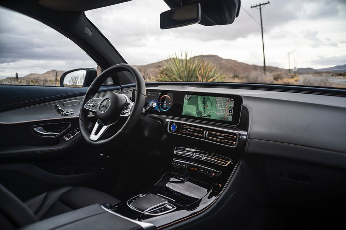 A view of the front seat and dashboard of a Mercedes-Benz EQC, showing a long touchscreen like the concepts with Mercedes' usual chrome-and-leather trim.