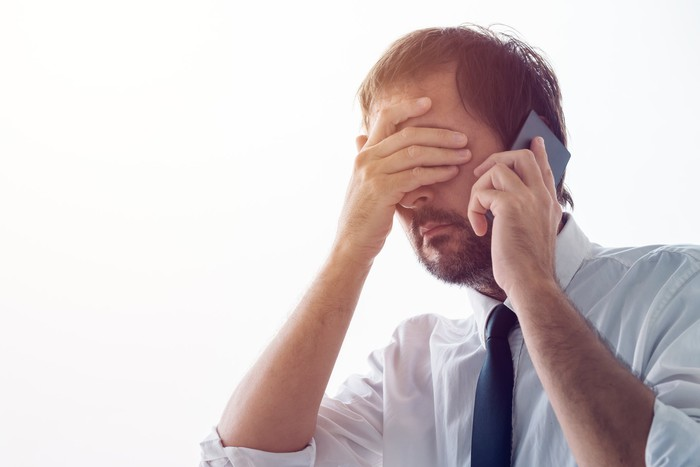Businessman with hand over face while talking on phone.
