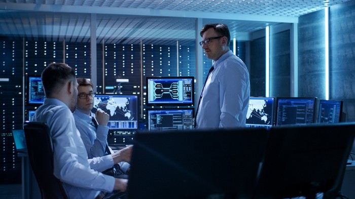 A hnadful of consultants and system administrators in a dark data center, surrounded by monitors and blinking lights.