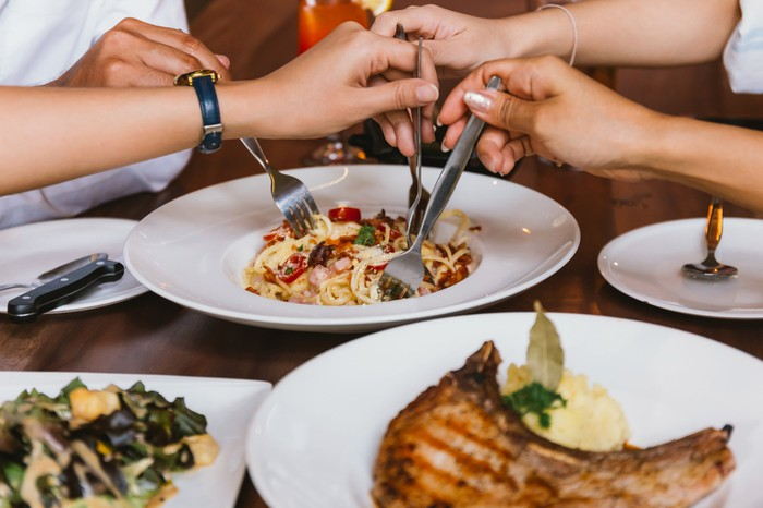 Friends plunge their forks into a shared plate of pasta at a fast-casual restaurant.