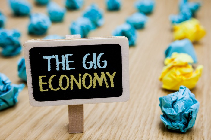 "A sign displaying ""The Gig Economy"" with pieces of crumpled paper in the background."