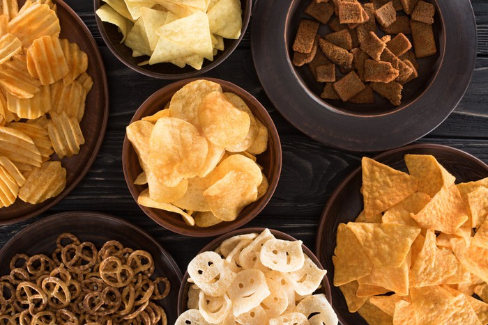 Chips, pretzels, and other snacks on a table.
