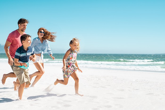 A family with kids is running on a beach.