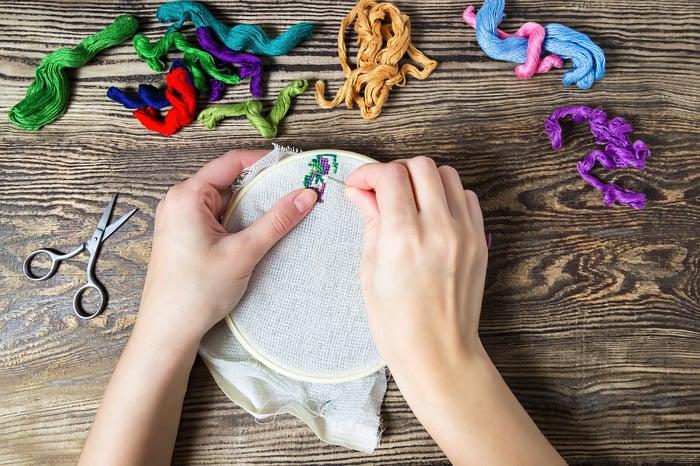 Hands beginning a design on an embroidery hoop