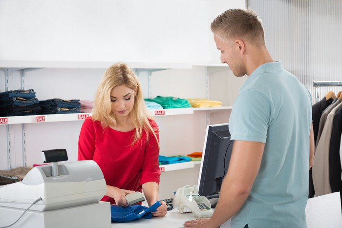 Female cashier scans clothing item at register while male customer looks on