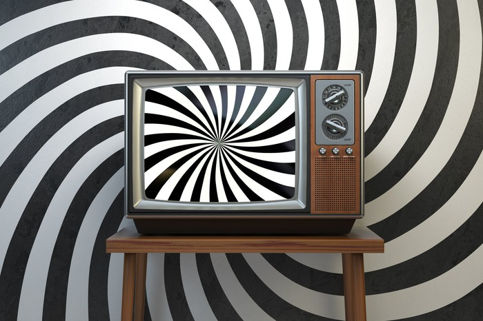 A TV showing a sprial pattern in front of a backdrop showing the same spiral pattern.