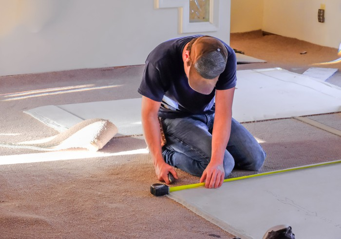 A male worker holding a measuring tape while kneeling on a floor with pieces of carpet.