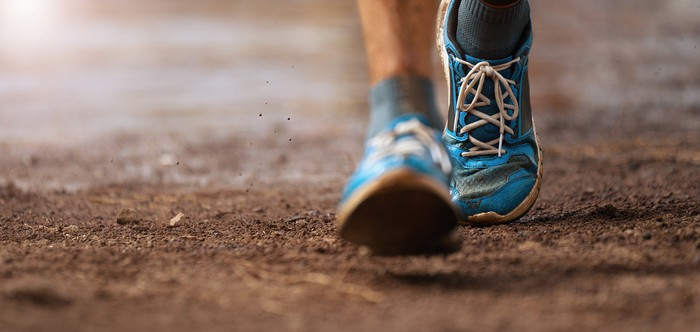 Close-up of two feet in athletic shoes walking an outdoor trail.