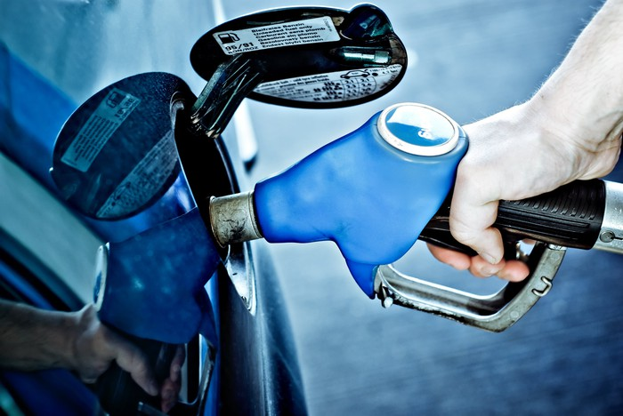 A person filling up their gas tank.