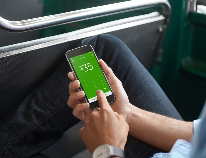 A person using Cash App on a smartphone.