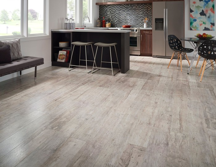 Large room with custom wood flooring along with other pieces of furniture.