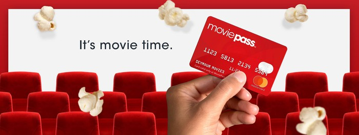 A MoviePass card being held up against falling popcorn in a movie theater.