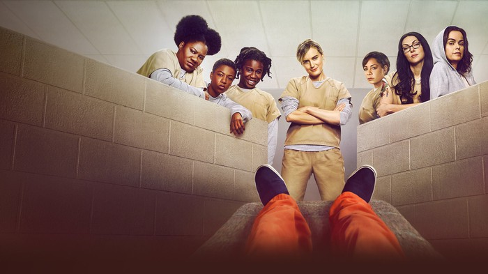 The cast of Orange is the New Black looking down at someone in an orange jumpsuit.