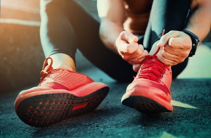 A jogger laces up her shoes before a run.
