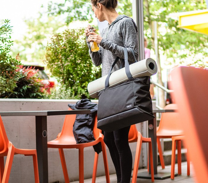 Woman with a Yeti tote and rolled up yoga mat