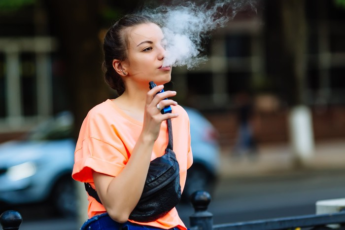 Young woman blowing smoke while holding a vaping device.