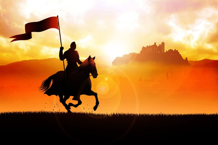 Knight carrying a flag and riding past a castle at sunset