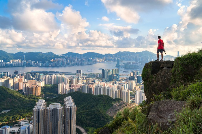 photographer standing on the top of Cliff above Hong kong cityscape.
