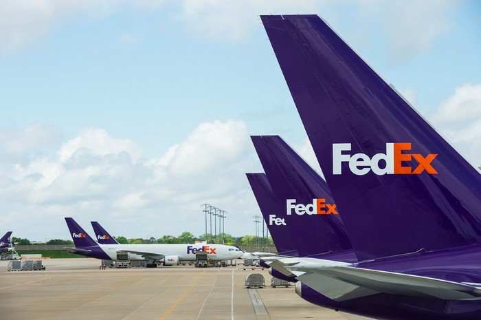 Several FedEx planes lined up on an airport ramp.
