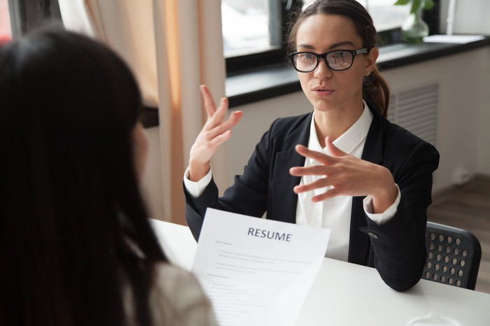 Professionally dressed woman gesturing while sitting across a table from another woman holding a resume