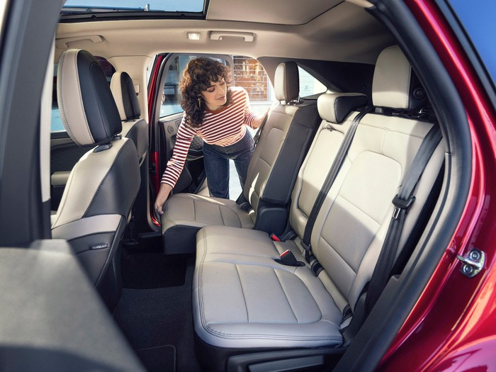 A woman moving the backseat of a red 2020 Ford Escape.
