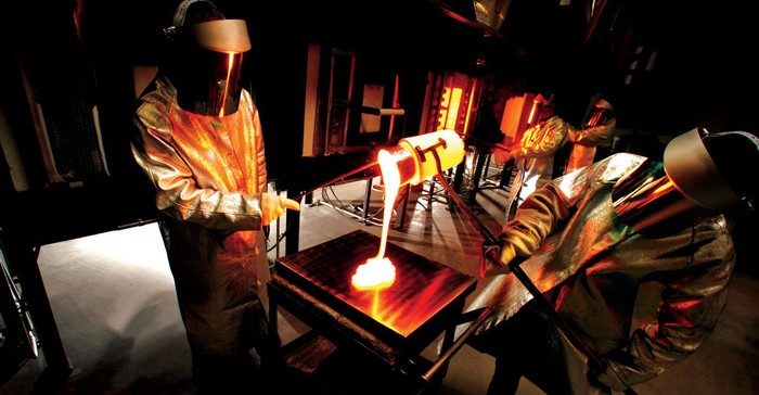 Corning scientists pouring molten glass wearing protective gear.