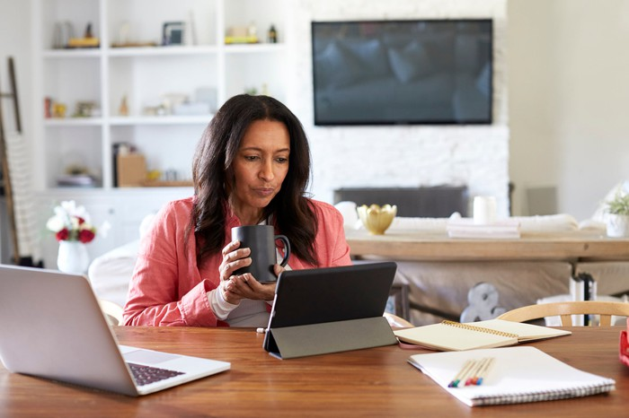 Woman sitting at table at home with tablet and laptop open.