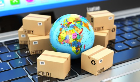 Shipping boxes surround a globe laying on a computer keyboard.