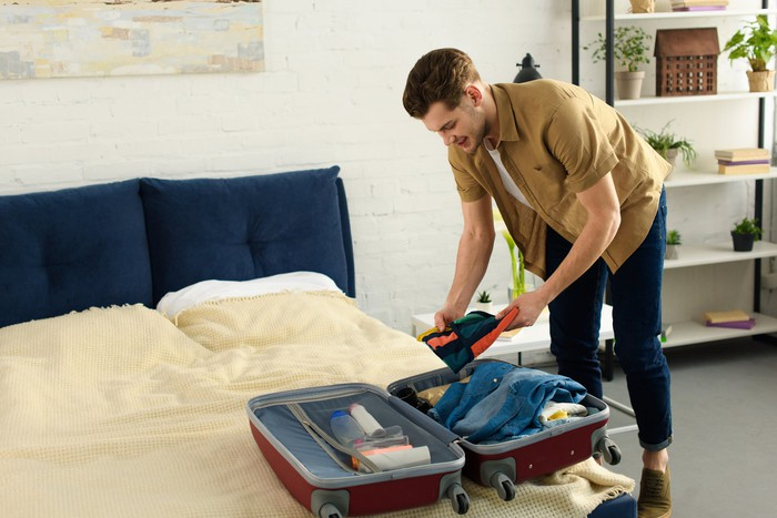 A man puts an item of clothing in an open suitcase spread out on a bed.